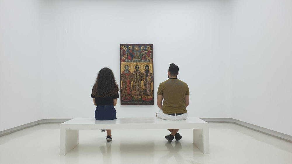 two persons sitting near each other and looking at artwork