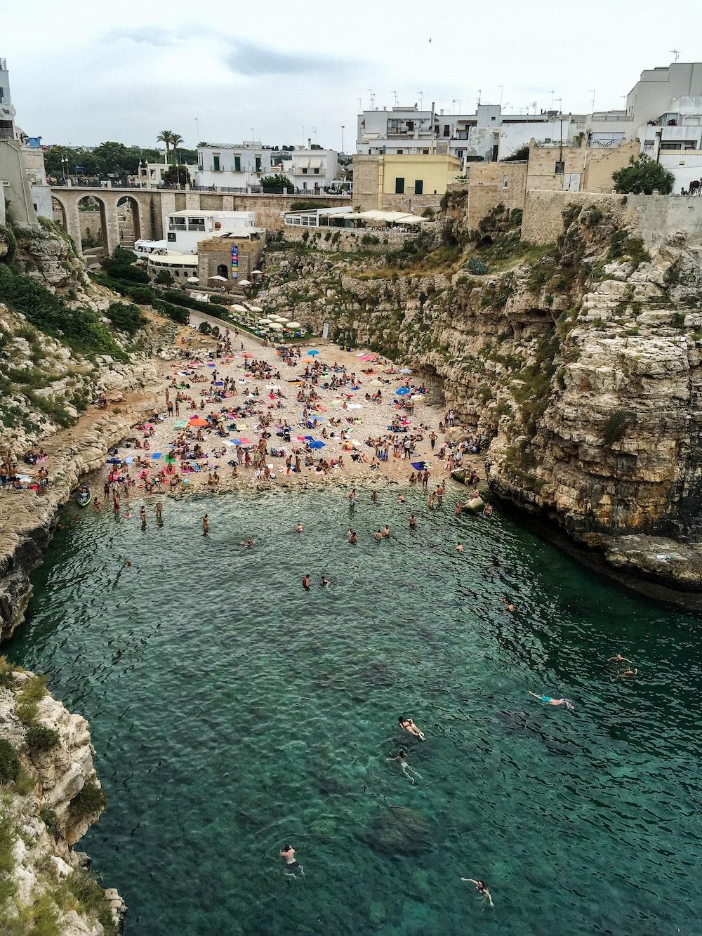 people in seashore near rocks