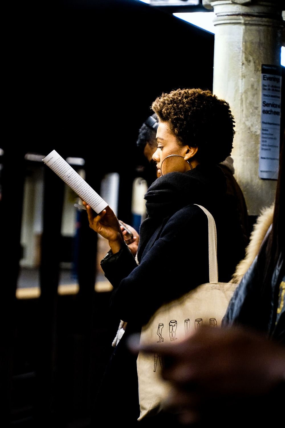 woman reading book while waiting in a train station