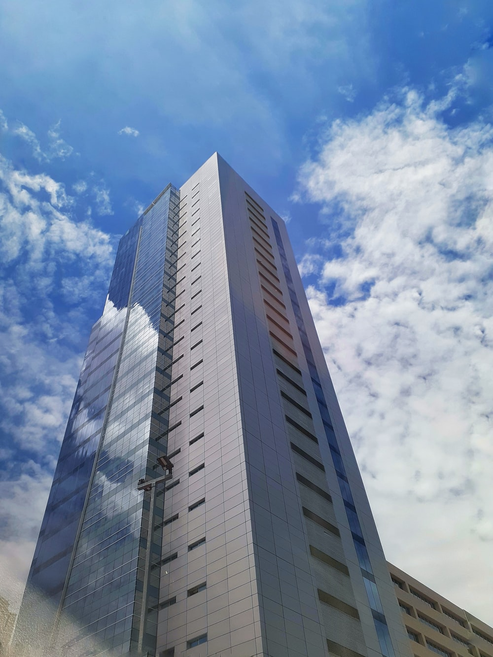 gray building under white clouds and blue sky