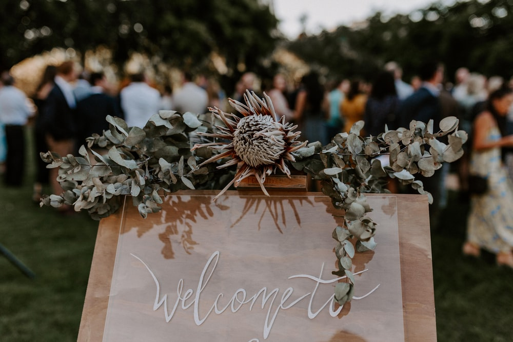 selective focus photography of welcome sign board