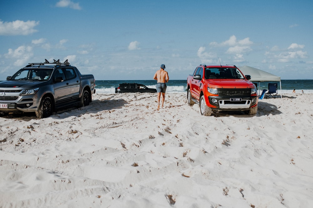 man standing between parked pickup trucks on sand seashore