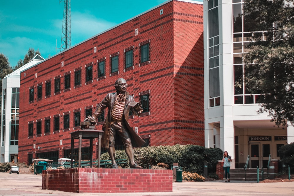 man statue near red building