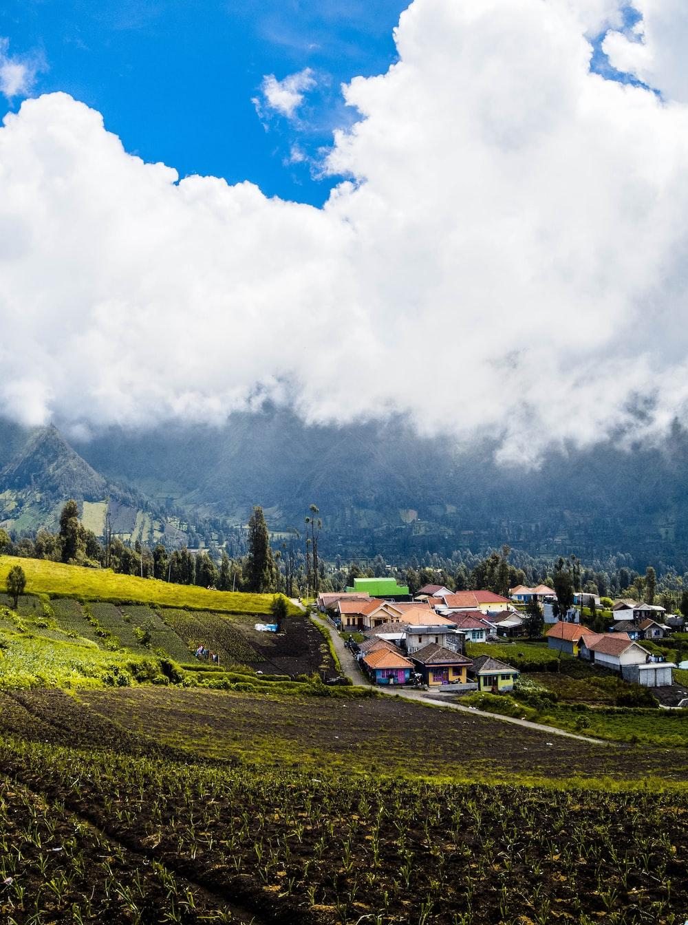 village on hill beside mountain ranges
