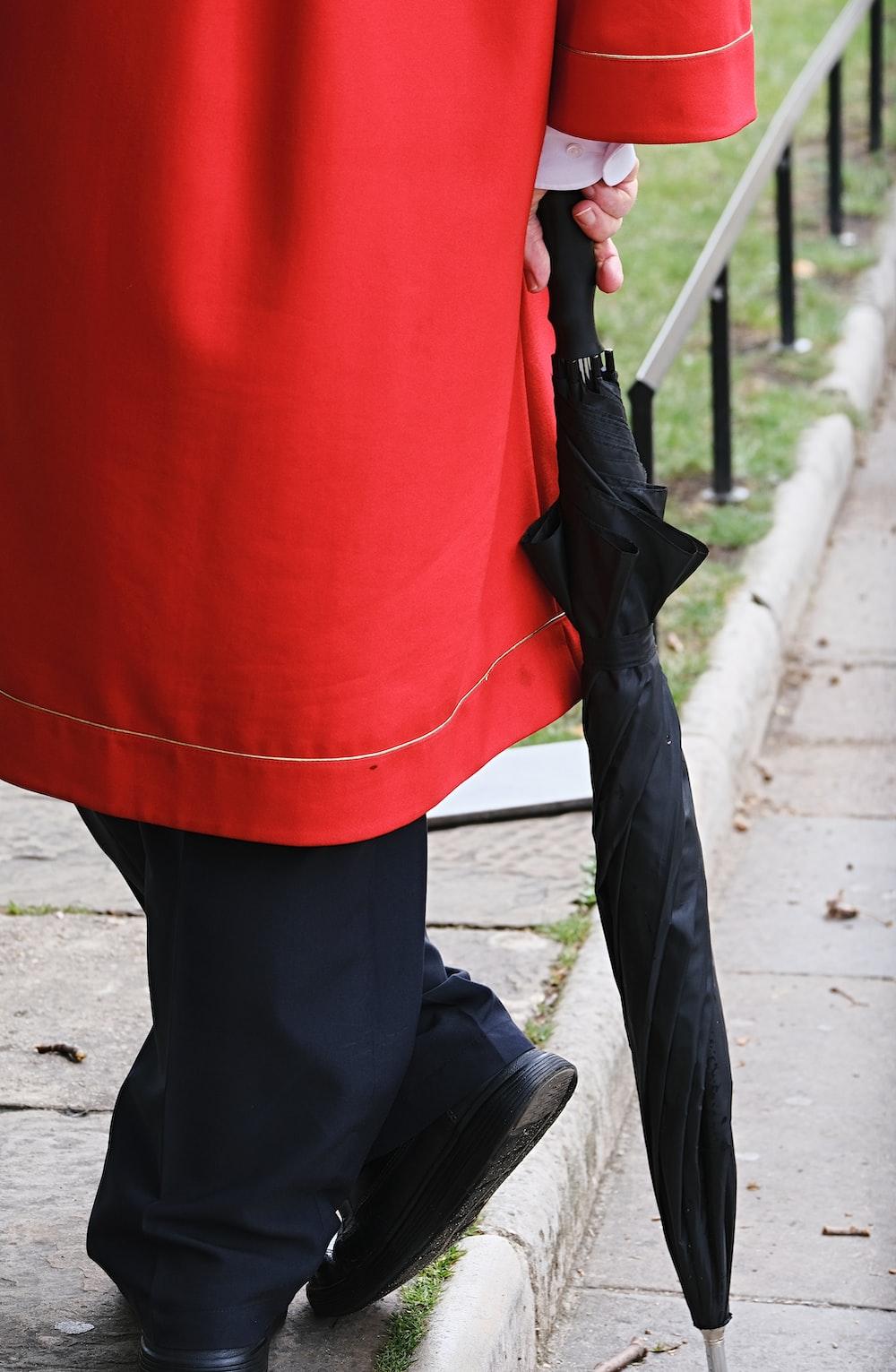 standing person holding black umbrella