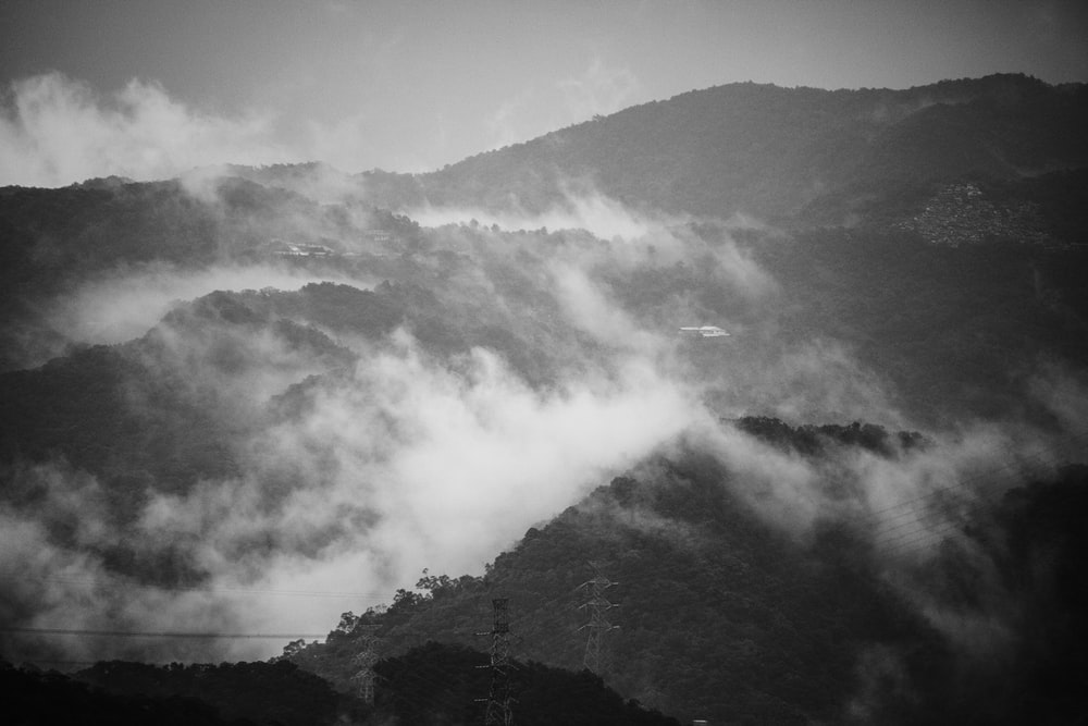 grayscale photography of mountain with clouds