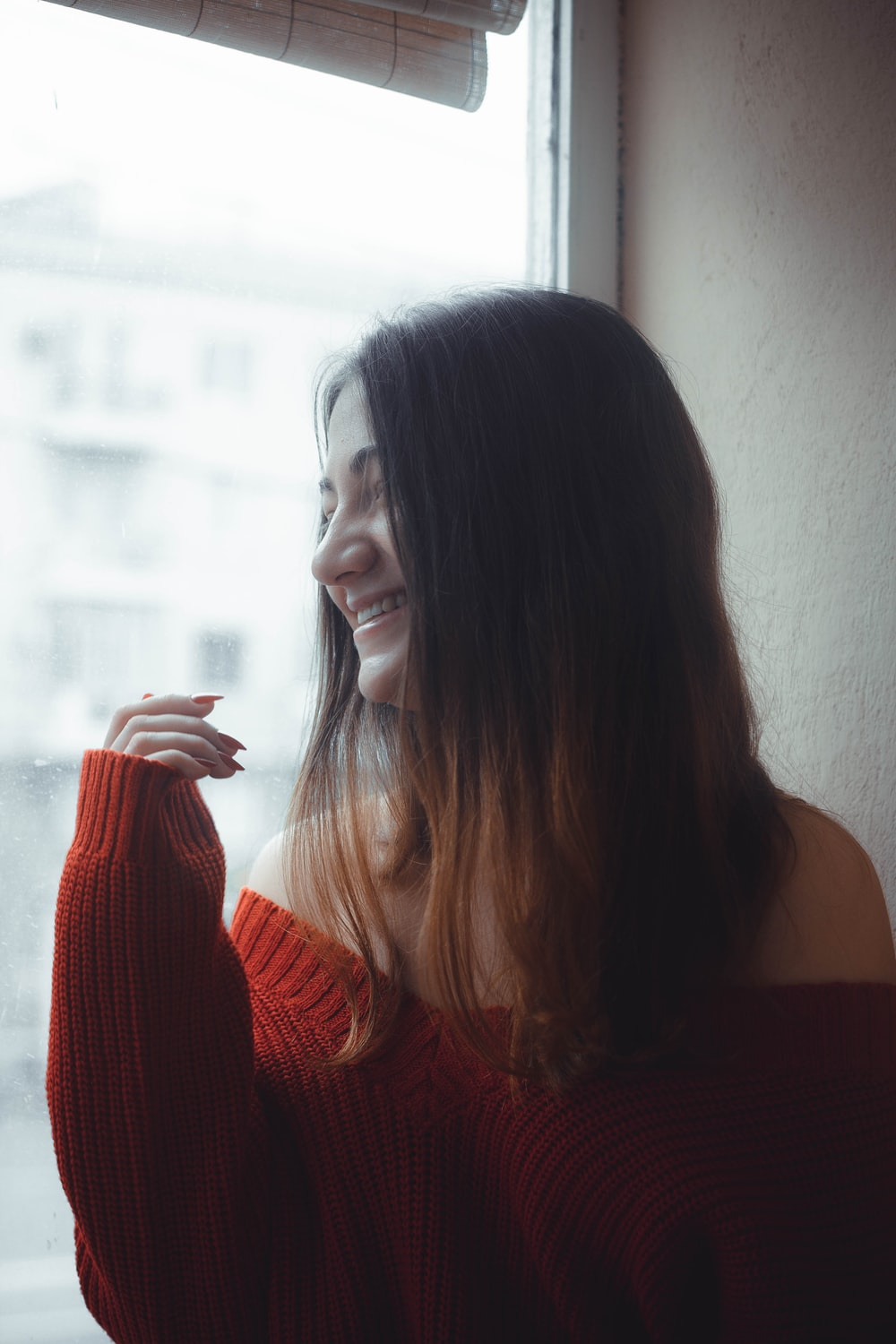 smiling woman in red off-shoulder sweater looking outside window
