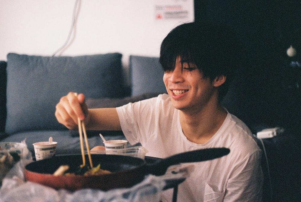 man using chopsticks to pickup food from pan