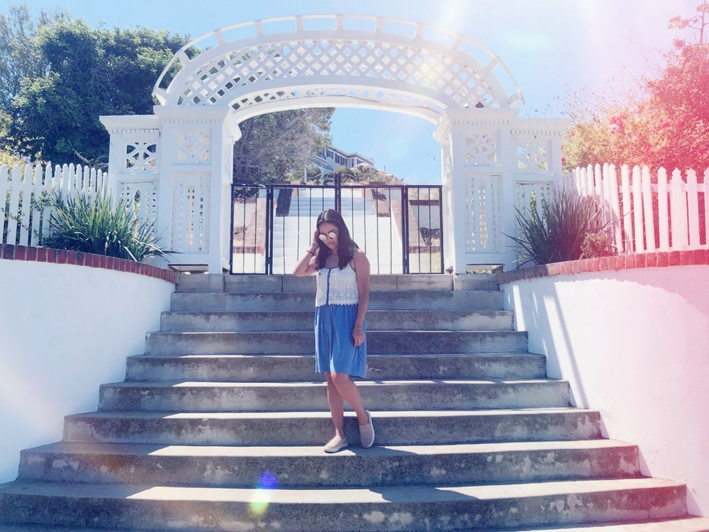 standing woman wearing white shirt and blue skirt on stairs