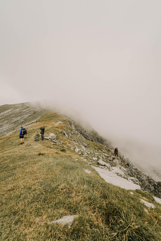 three person walking on hill