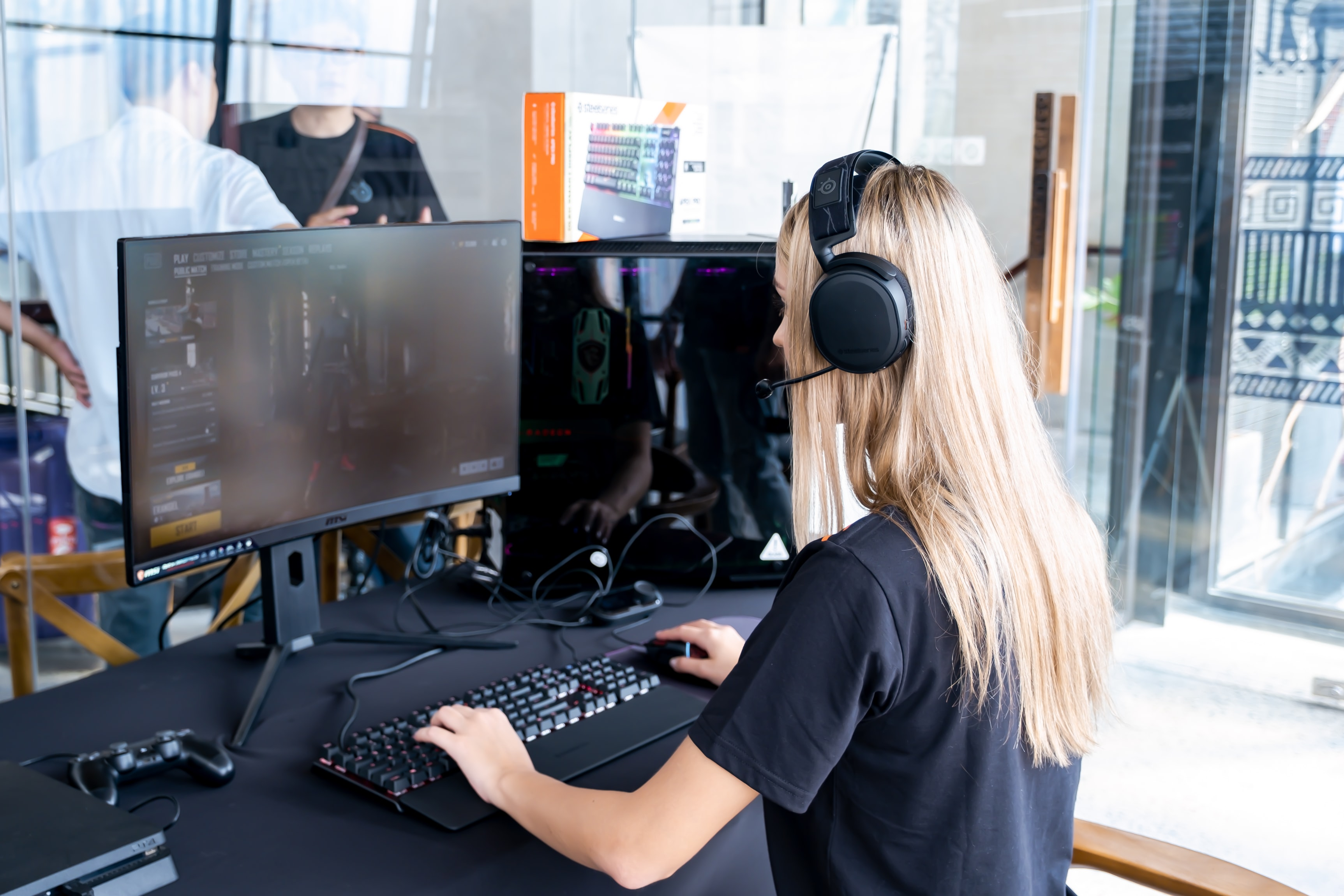 Woman with headset playing a video game on computer