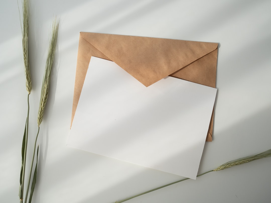 white invitation and envelope on a table.