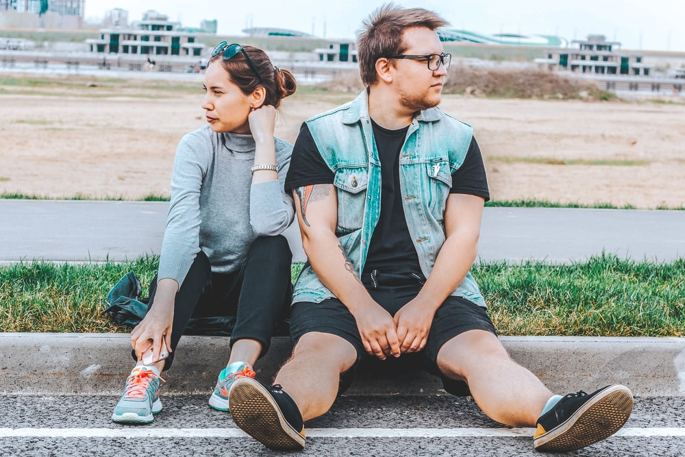woman looking at her right sitting at curb beside man looking at his left