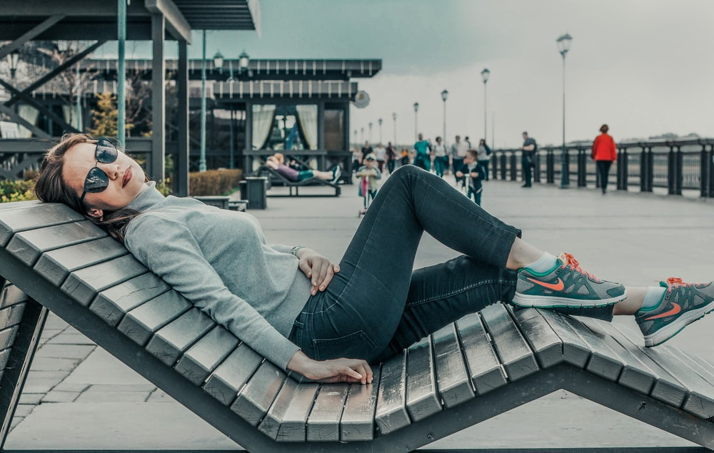 woman laying on bench during daytime