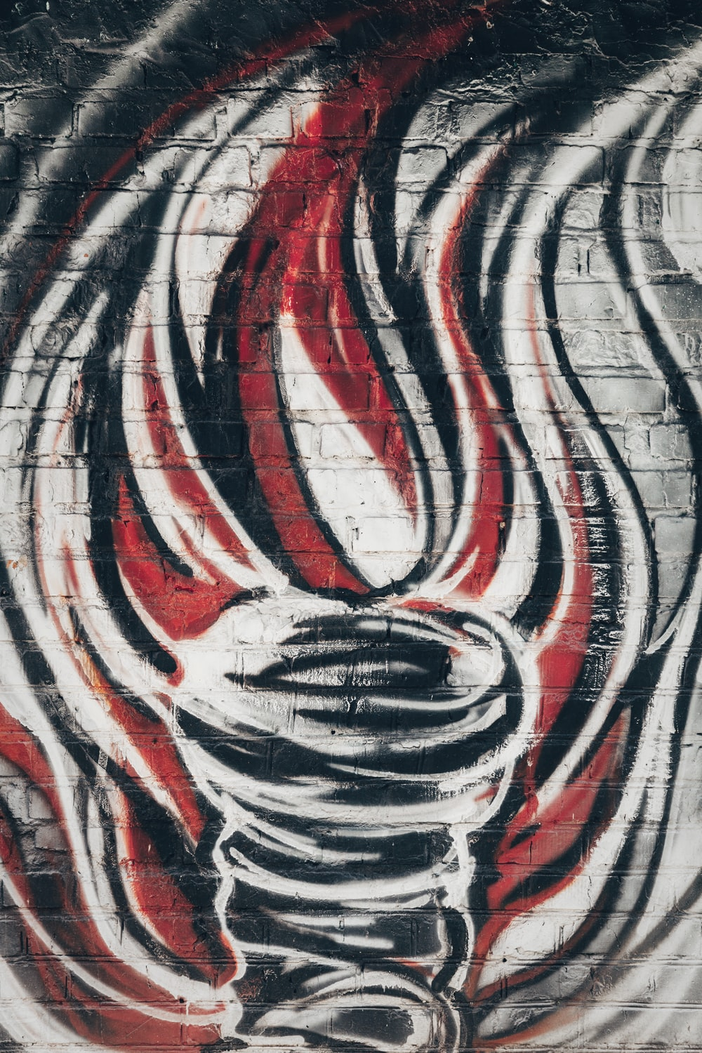 gray, red and black graffiti on a wall