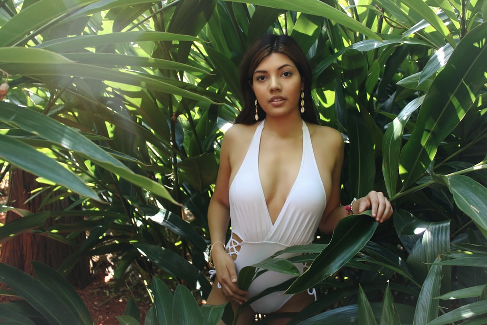 woman wears white halter monokini behind bushes