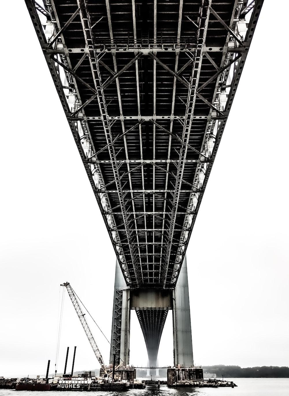 boats under black metal bridge at daytime