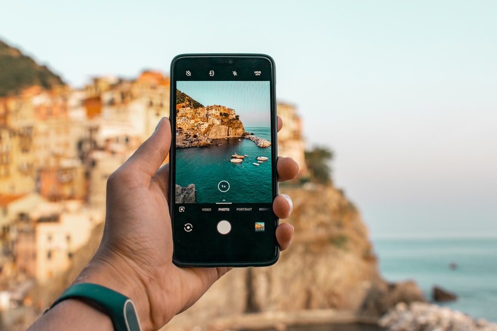 person holding a phone near cliff during daytime