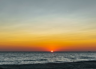 sea under gray sky during golden hour
