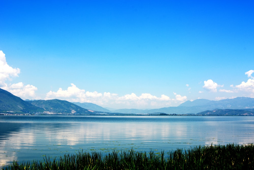 body of water near hills under white clouds and blue sky during daytime