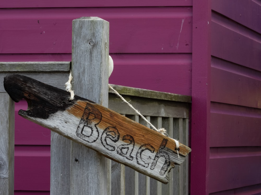 brown wooden signboard hanged in a fence near a purple wall