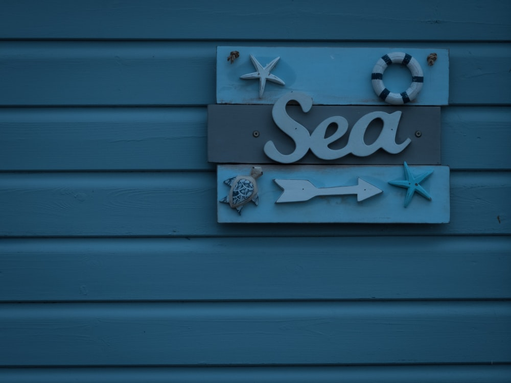 blue and brown sea signboard on wall