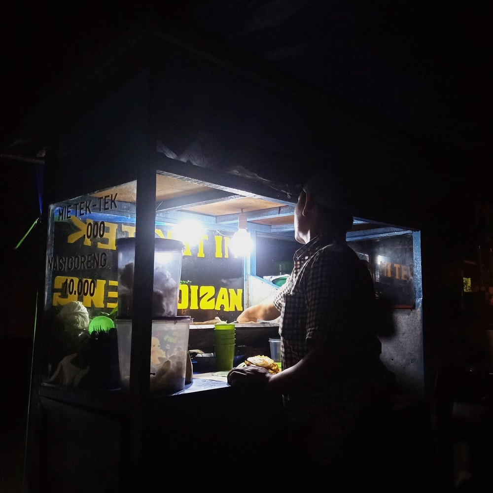 man standing in front of food cart during night time