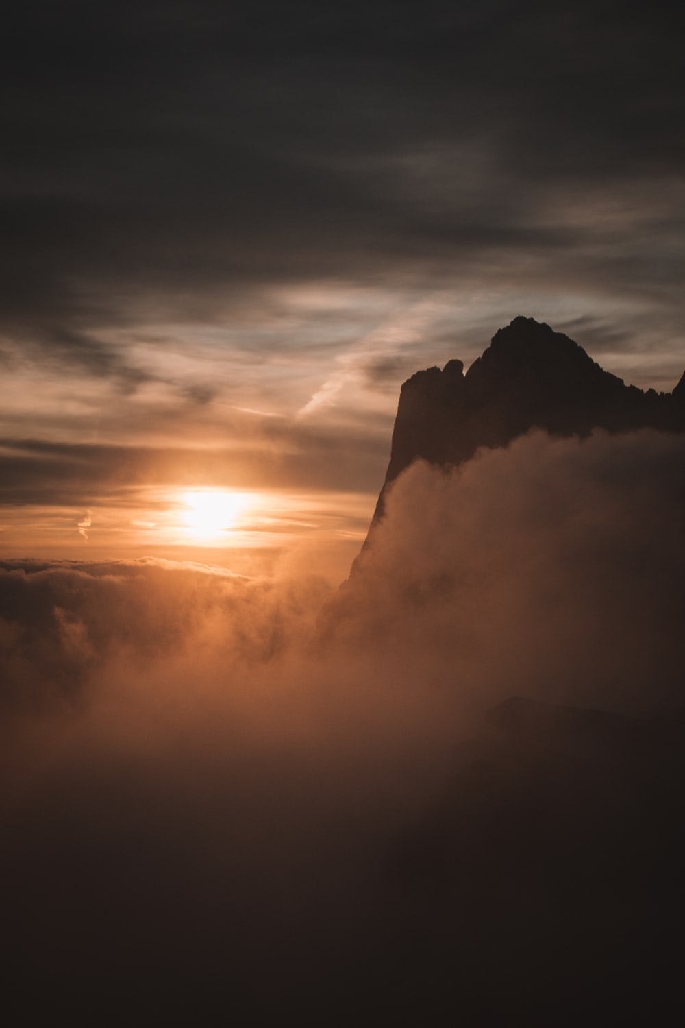 silhouette of mountain under cloudy sky