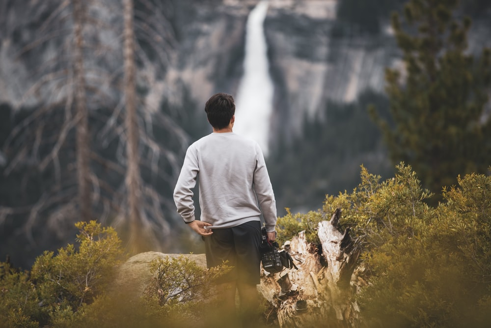 selective focus photography of standing man in gray shirt overlooking waterfalls