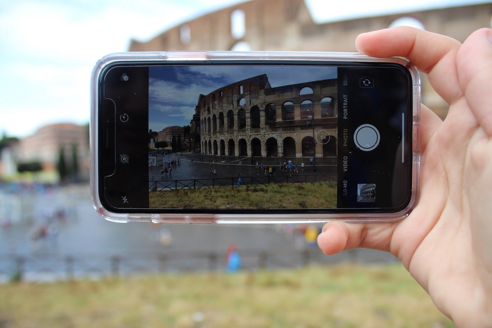 person holding black smartphone taking photo