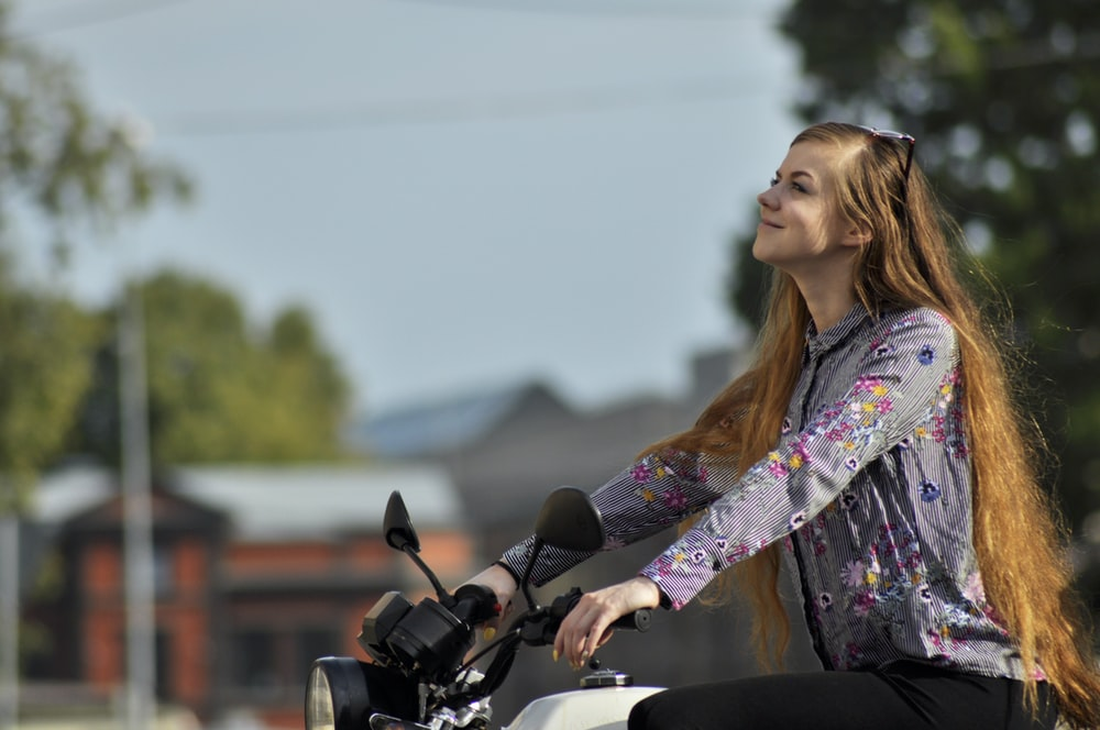 woman wearing purple floral long-sleeved top riding motorcycle
