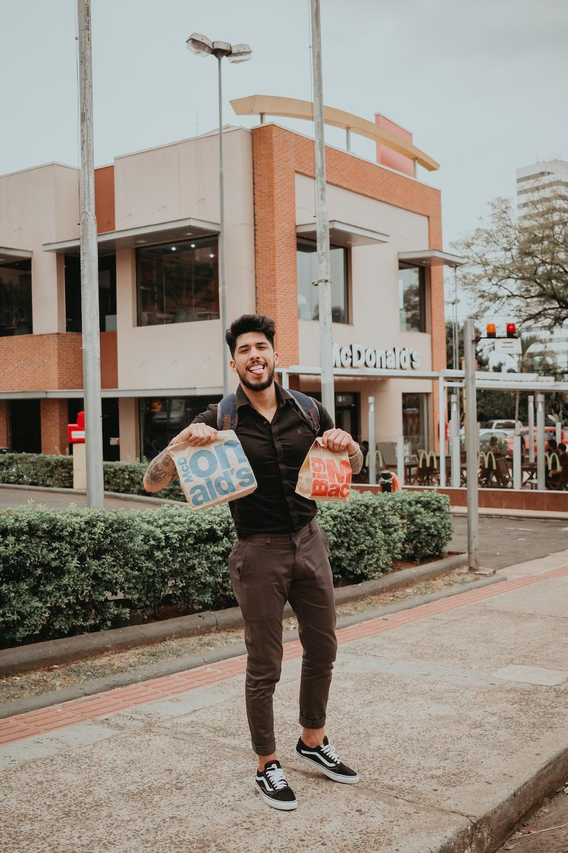man wearing black dress shirt holding 2 MacDonalds paper bags