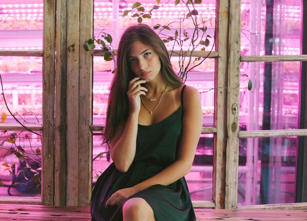 woman wearing green dress sitting near window