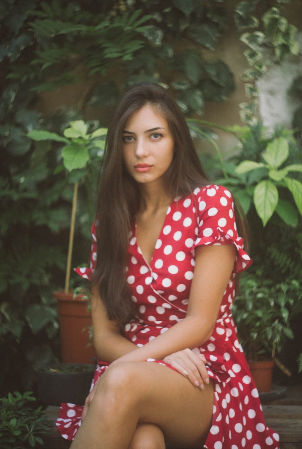 woman sitting in front of leafed plants