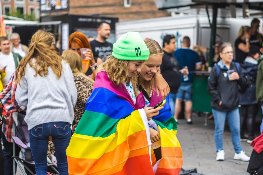 two women covering themselves of LGBTQ flag