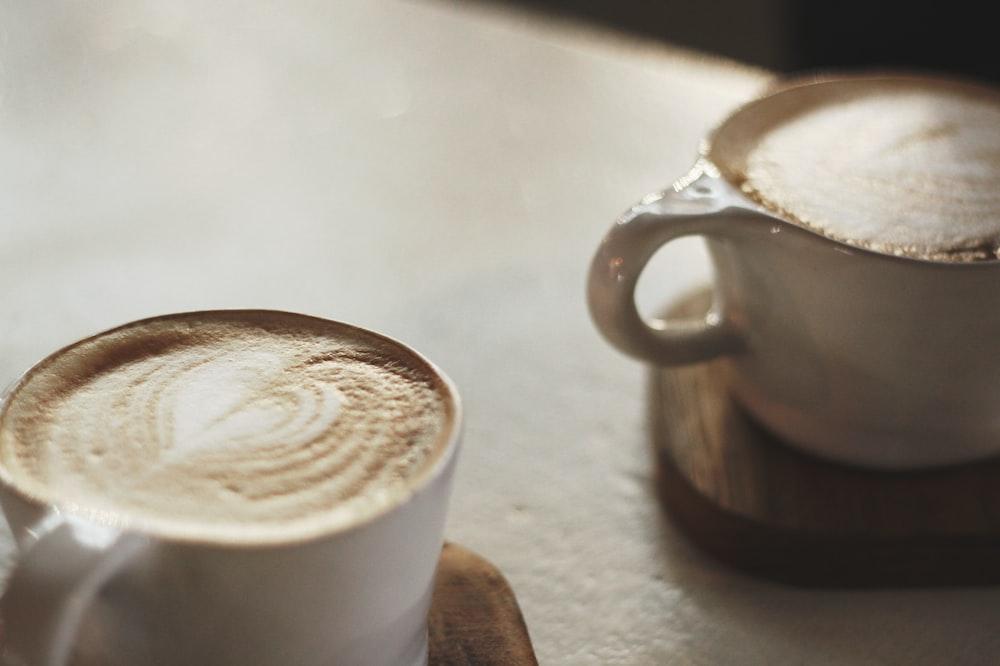 two white ceramic mugs on coaster