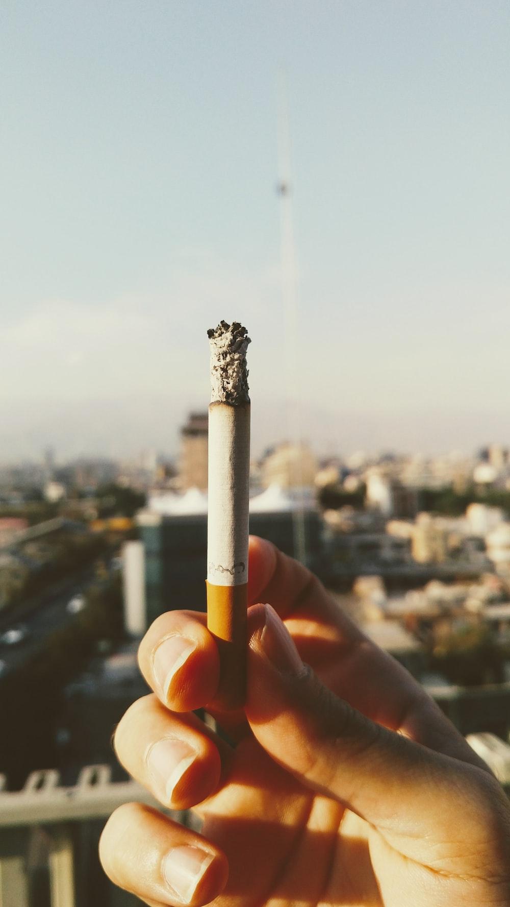person holds cigarette stick
