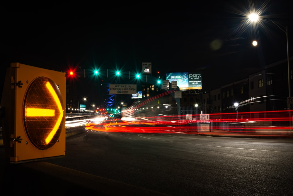 timelapse photography of vehicle traveling on road during nighttime
