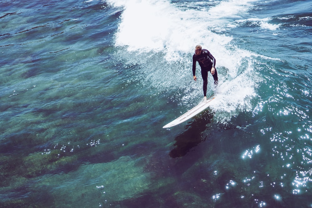 man riding on white surfboard about to surf on ocean waves