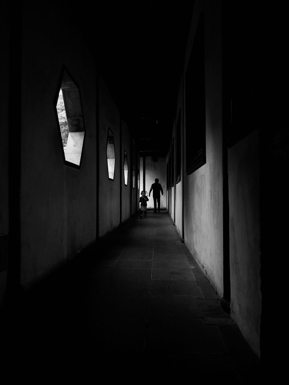 grayscale photography of two person walking on hallway