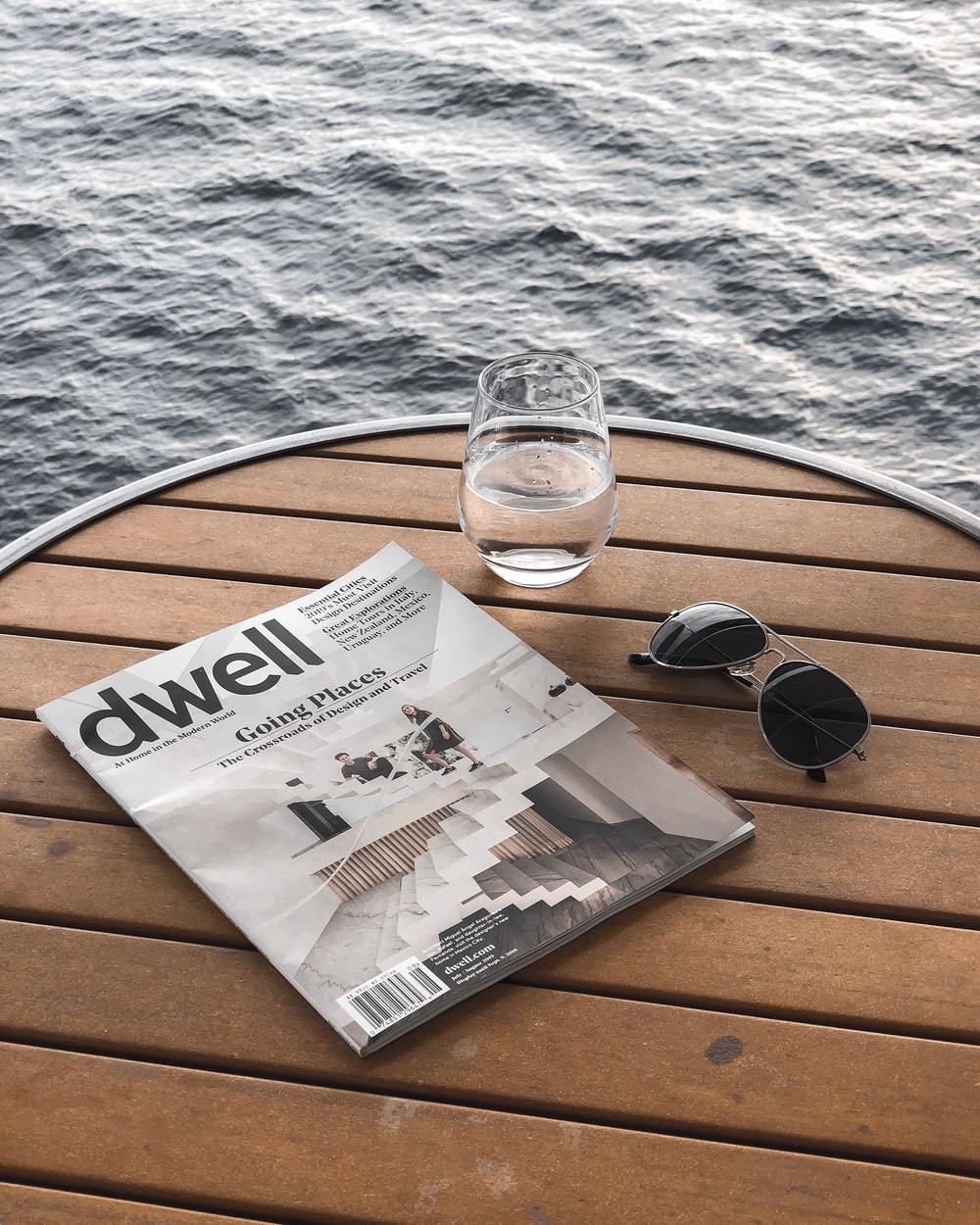 cup of water beside magazine and sunglasses