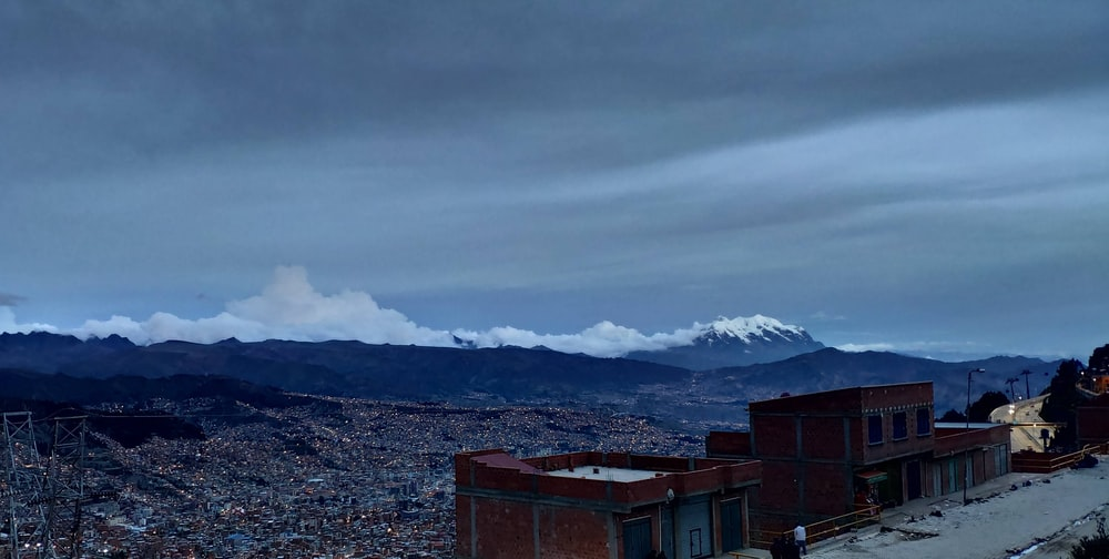 brown buildings near snow-capped mountain