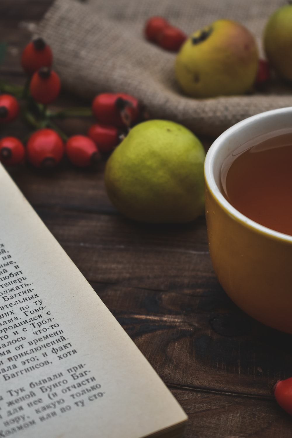 filled cup near fruits and book