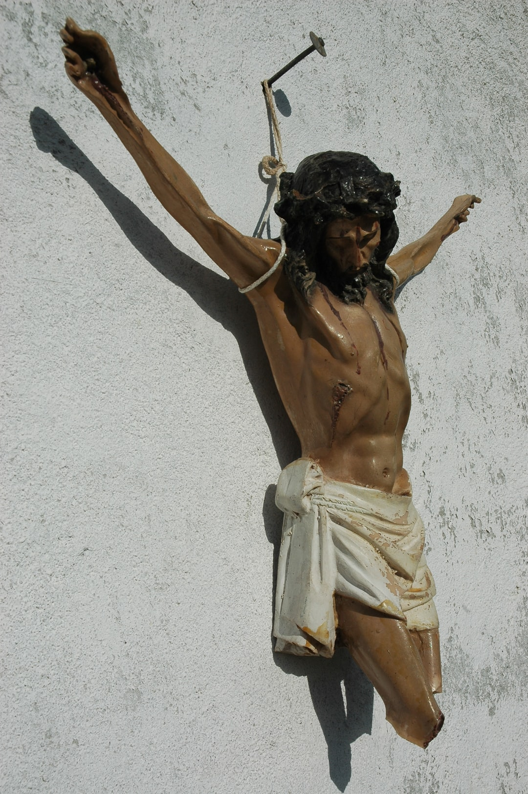 Broken statue of Christ crucified, nailed to a wall with string supporting His arms, abandoned object, reused on a countryside outdoor folk shrine, faith, love, Hermosillo, Senora, Mexico