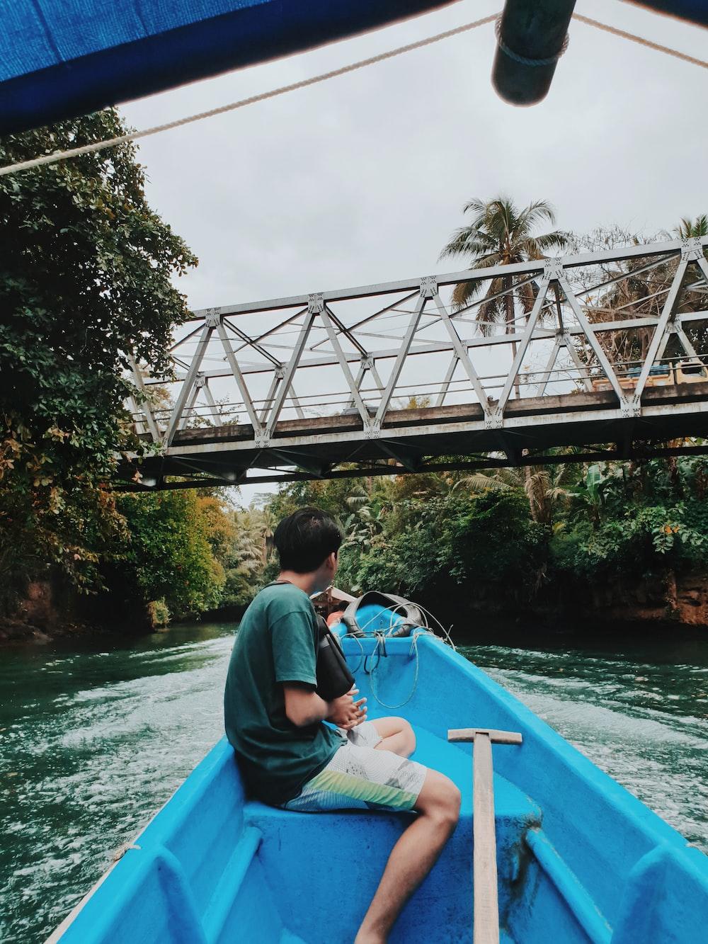 boy sitting on boat near bridge