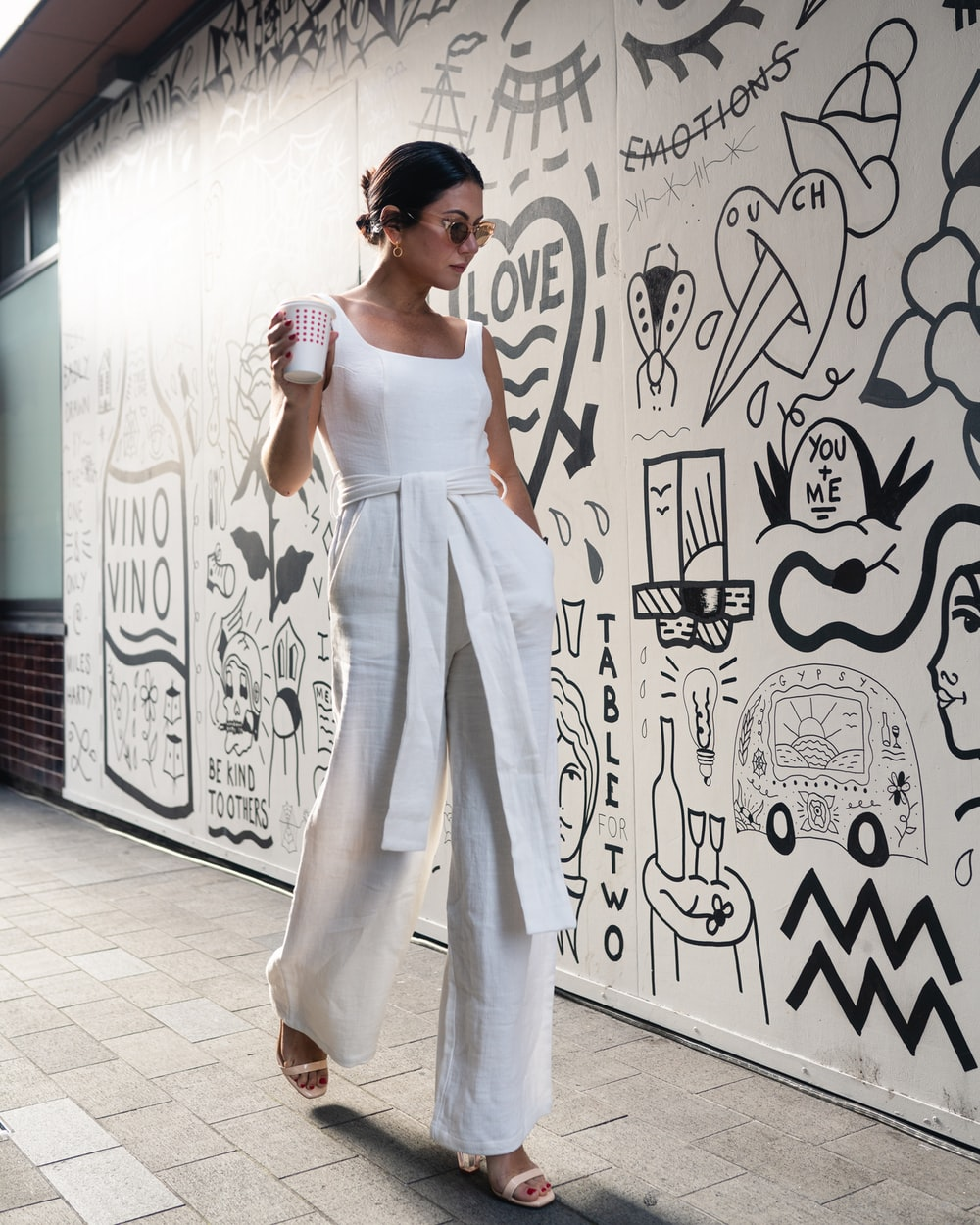 woman holding cup walking beside wall