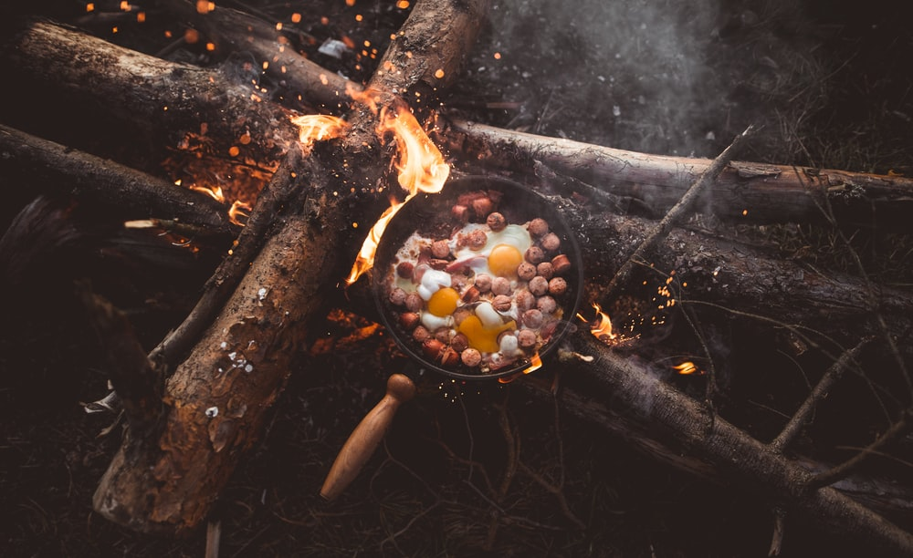 frying pan with food on lit firewood