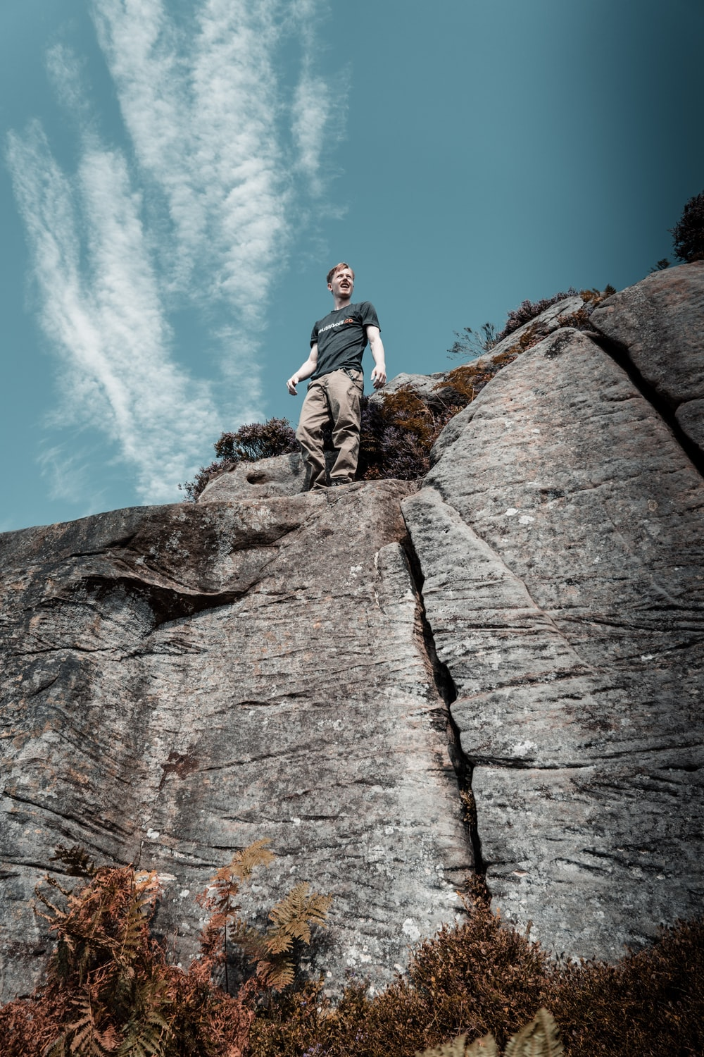 low-angle photography of man standing on a mountain cliff
