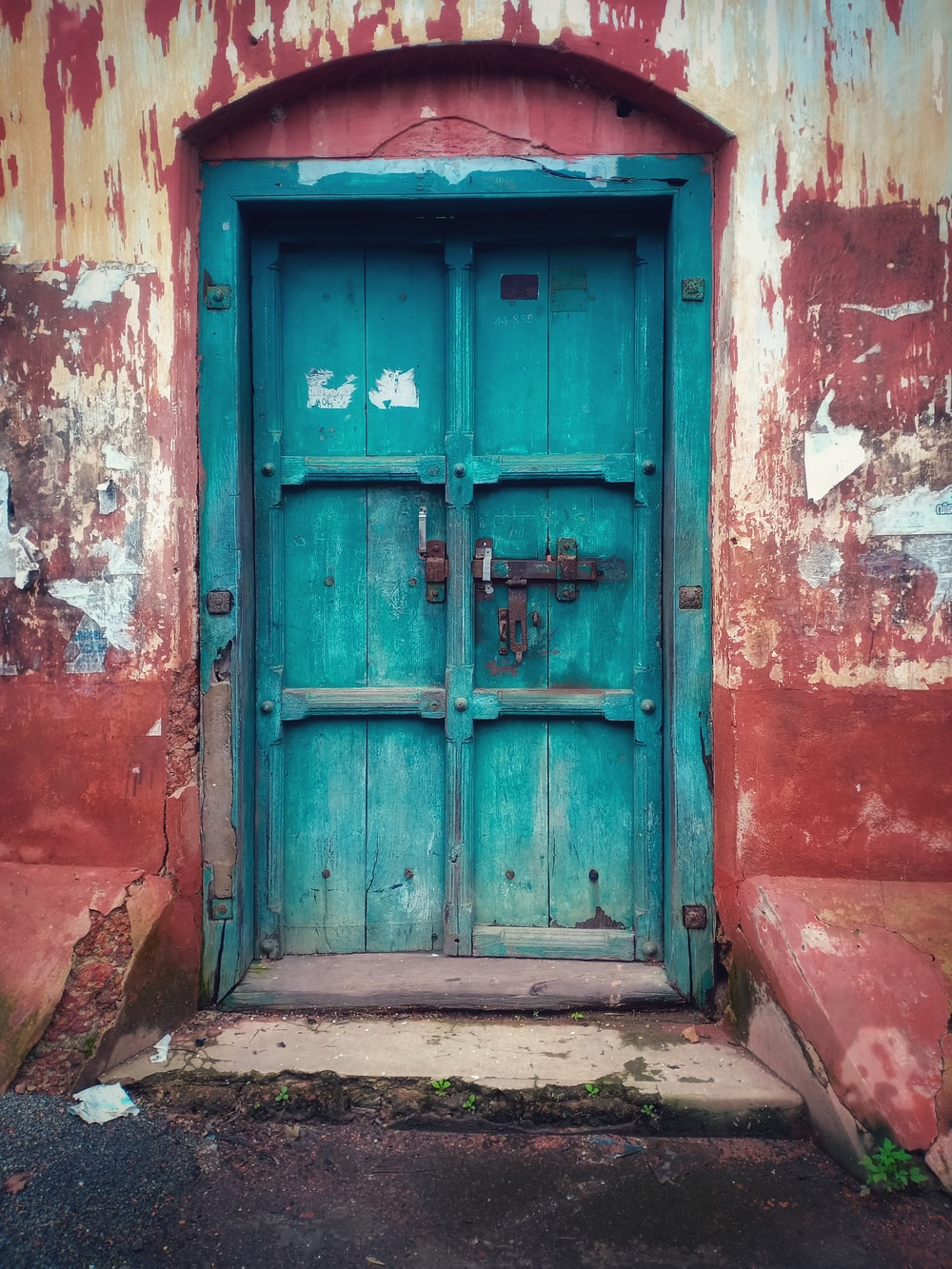 brown concrete building with blue wooden closed door