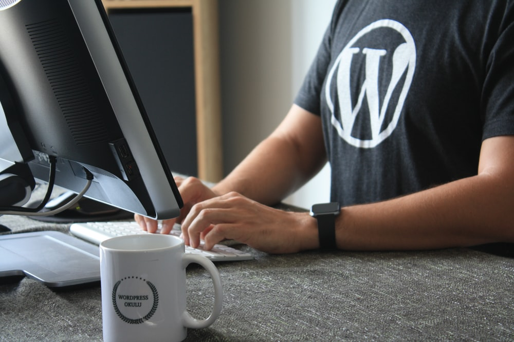 person in black and white t-shirt using computer